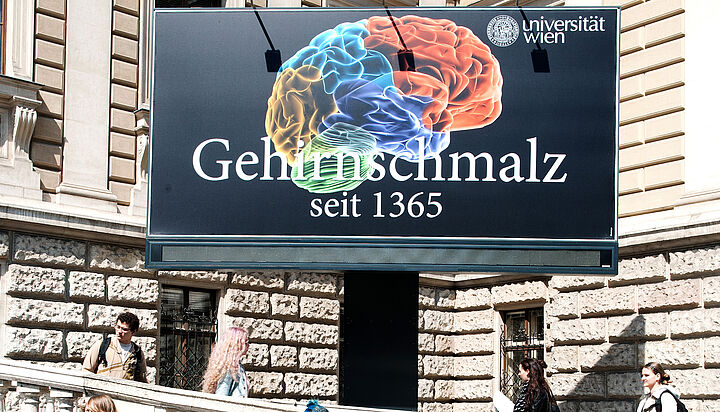 "the billboard ""Gehirnschmalz. Seit 1365"" in front of the Main Building"